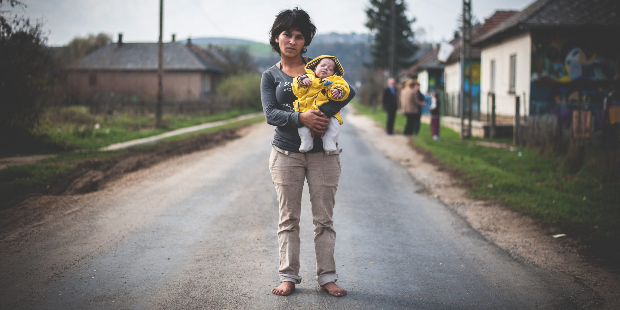 Woman stands with her child in Bódvalenke, Hungary