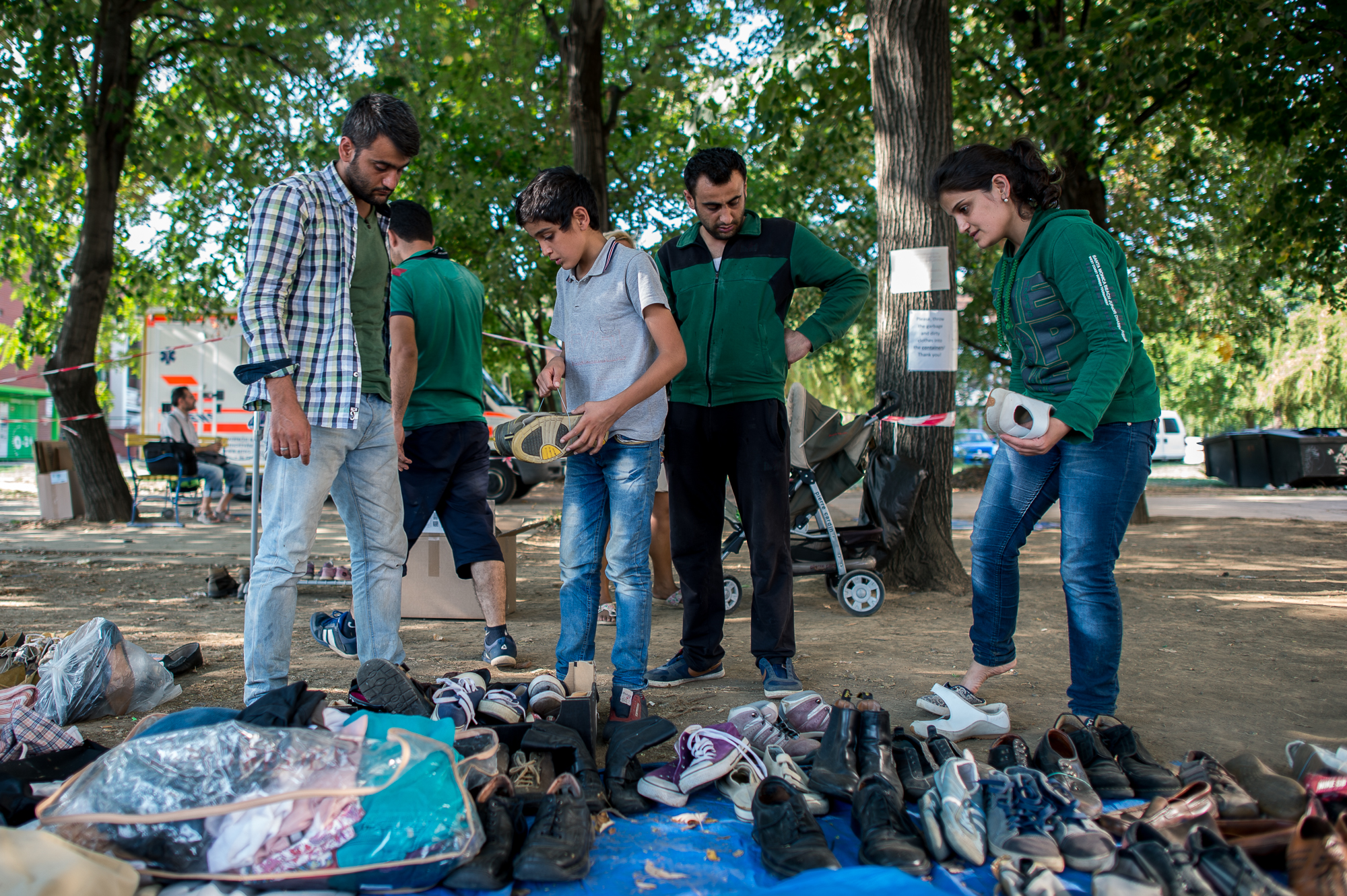 Szír menekültek nézik az adományozott ruhadarabokat a civilek által működő várakozó helyen a pécsi vasútállomás mellett 2015. augusztus 31-én.