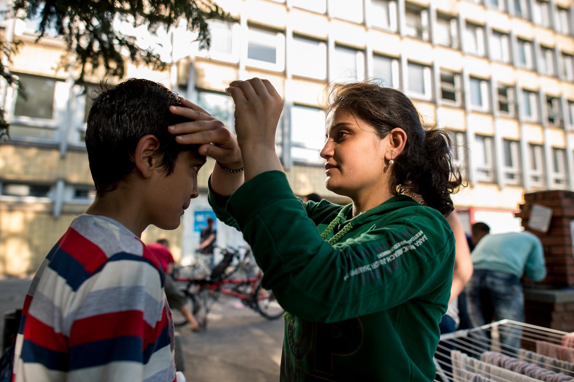 Egy szír menekült igazítja meg testvére haját a civilek által működő várakozó helyen a pécsi vasútállomás mellett 2015. augusztus 31-én.