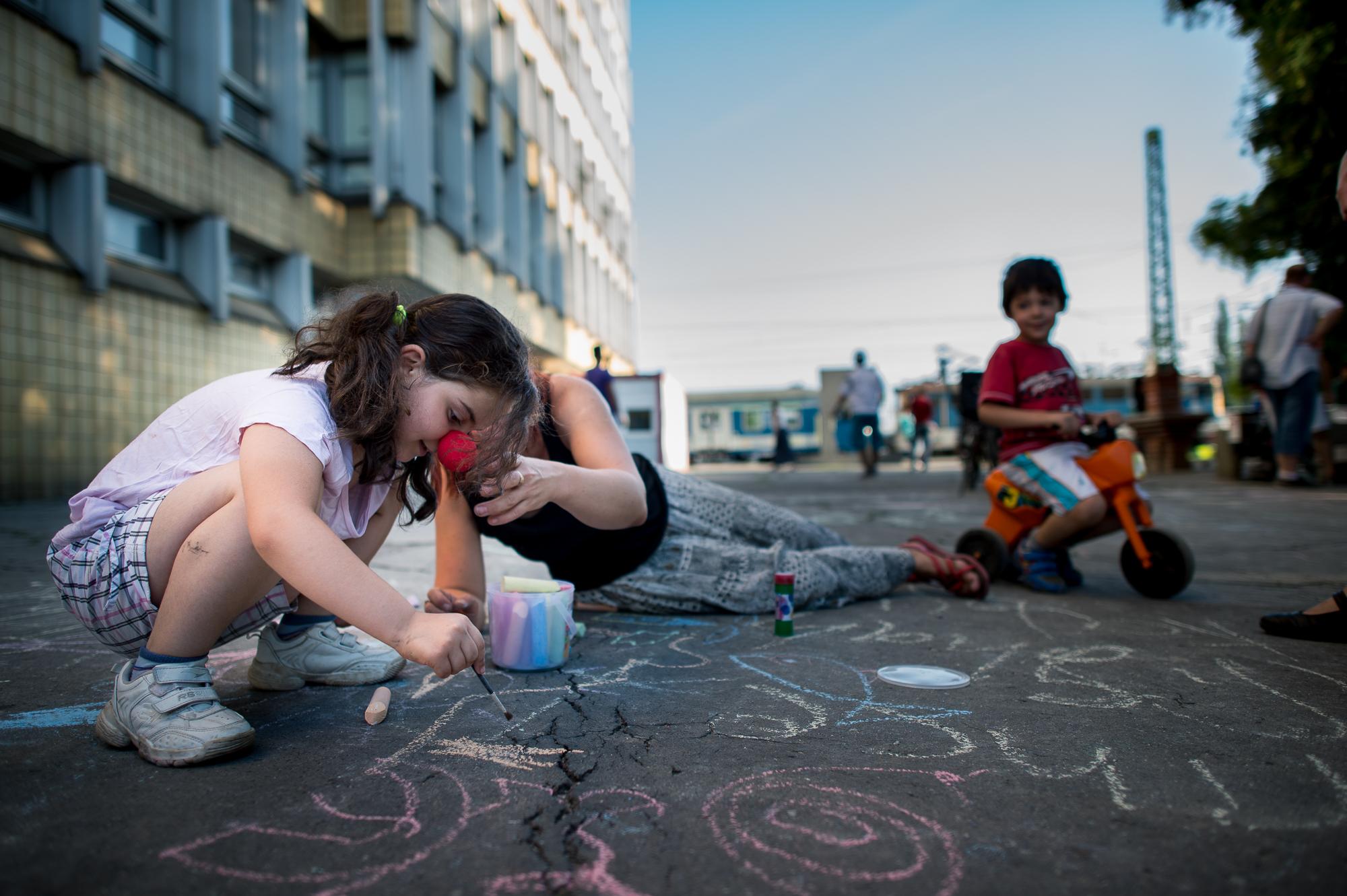 Egy szír menekült kislány rajzol az asztfaltra a civilek által működő várakozó helyen a pécsi vasútállomás mellett 2015. augusztus 31-én.