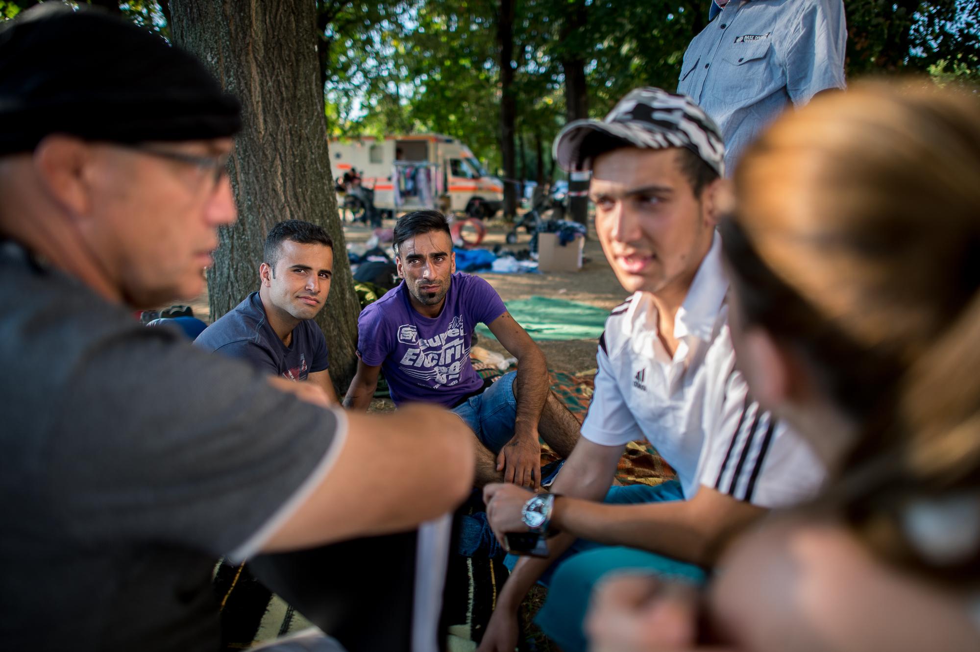 Szír menekültek beszélgetnek önkéntesekkel a civilek által működő várakozó helyen a pécsi vasútállomás mellett 2015. augusztus 31-én.