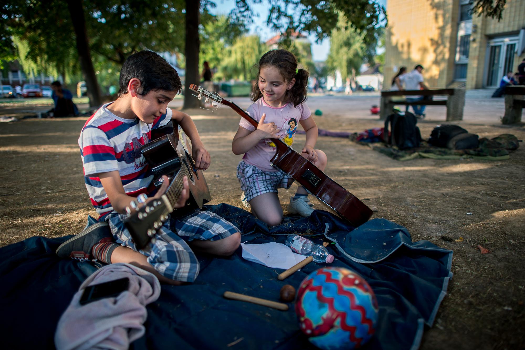Szír menekült fiatalok zenélnek a civilek által működő várakozó helyen a pécsi vasútállomás mellett 2015. augusztus 31-én.