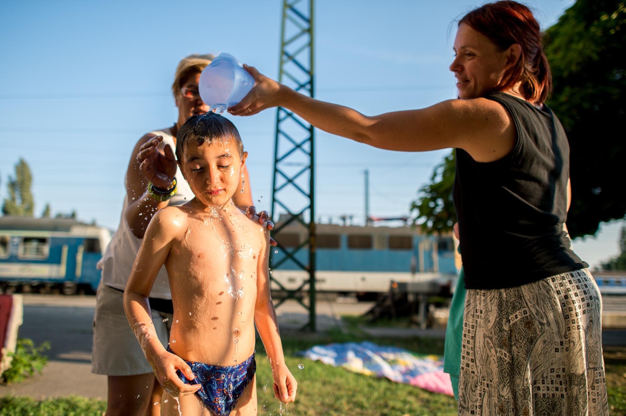 Egy menekült kisfiút fürdetnek önkéntesek a civilek által működő várakozó helyen a pécsi vasútállomás mellett 2015. augusztus 31-én.