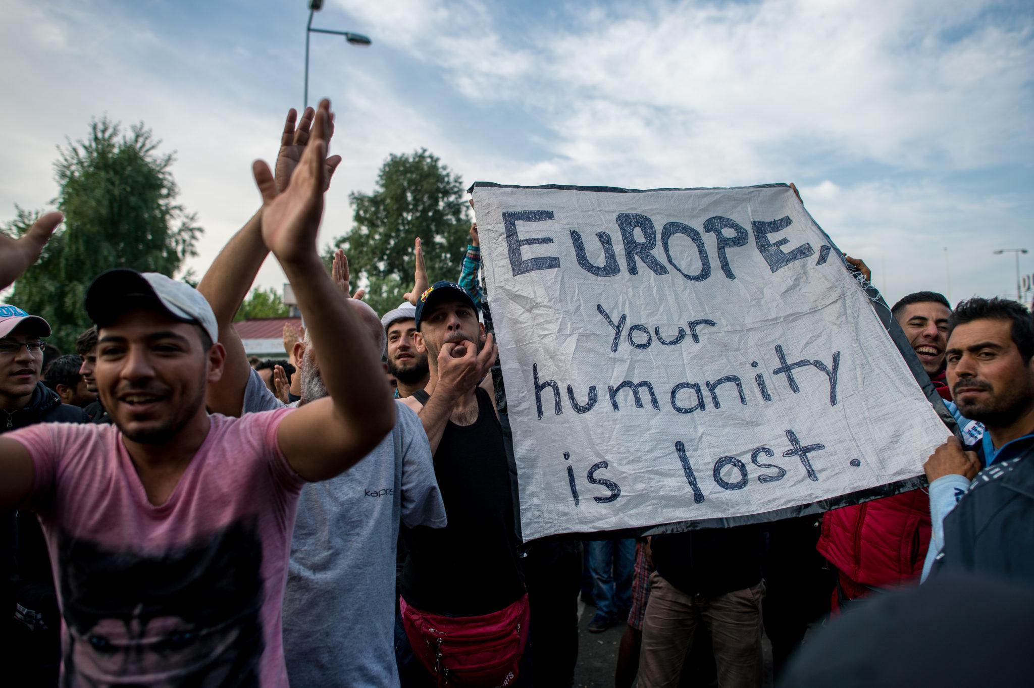 Migránsok egy transzparenst tartanak a röszkei határátkelőhelynél Horgos Közelében 2015. szeptember 15-én.