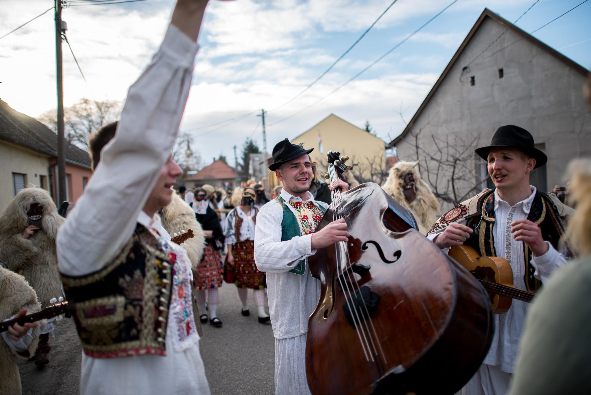 Sokác népviseletbe öltözött zenészek mennek házalni a mohácsi busójárás ötödik napján 2019. március 4-én.